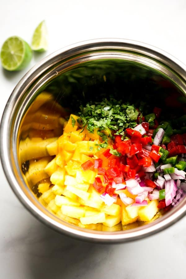 A bowl of pineapples, mangoes, red bell pepper, red onions, cilantro