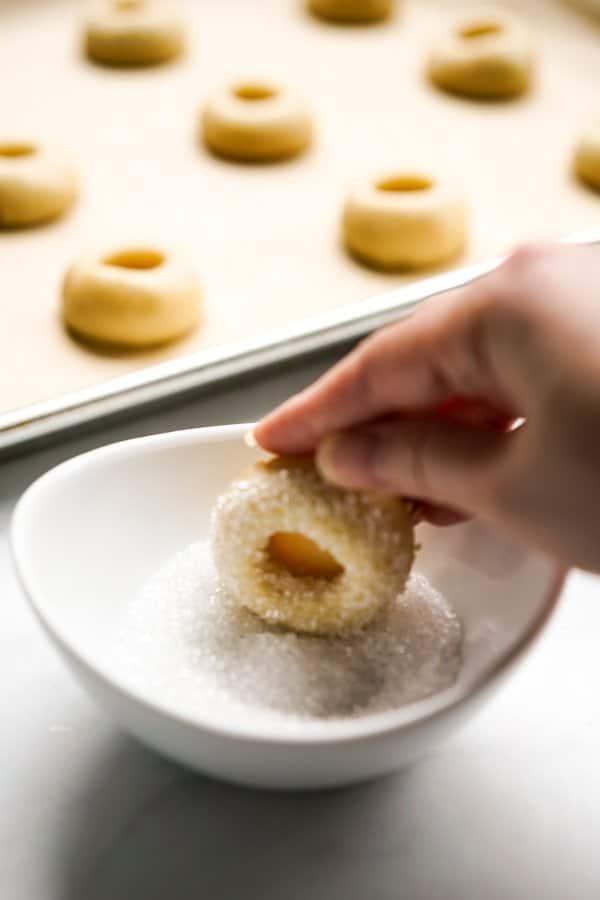 Dipping indented shortbread cookie dough into sugar crystals