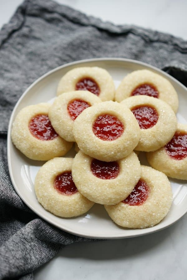 A stack of strawberry shortbread thumbprint cookies