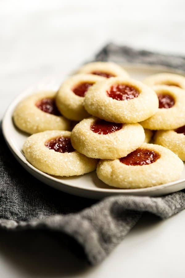 Shortbread thumbprint cookies filled with strawberry jam stacked on a plate