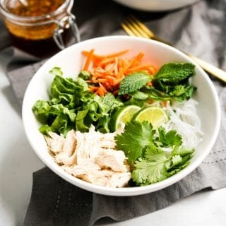 A bowl of rice noodles topped with lettuce, cilantro, mint leaves, carrots and chicken