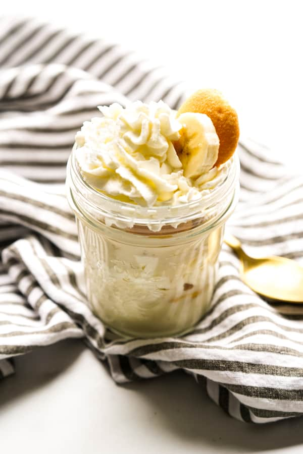 Layers of banana pudding in an individual jar topped with whipped cream, bananas and wafers