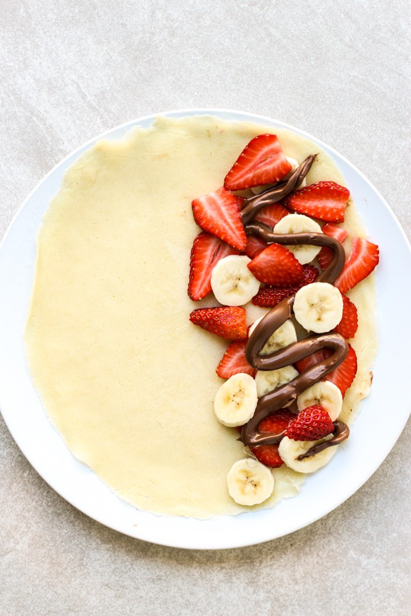 Adding strawberries, bananas and drizzles of nutella onto crepe