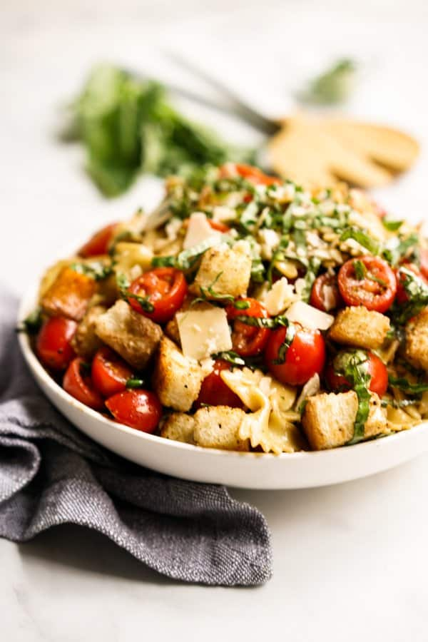 A plate of pasta salad with croutons, tomato, basil and parmesan