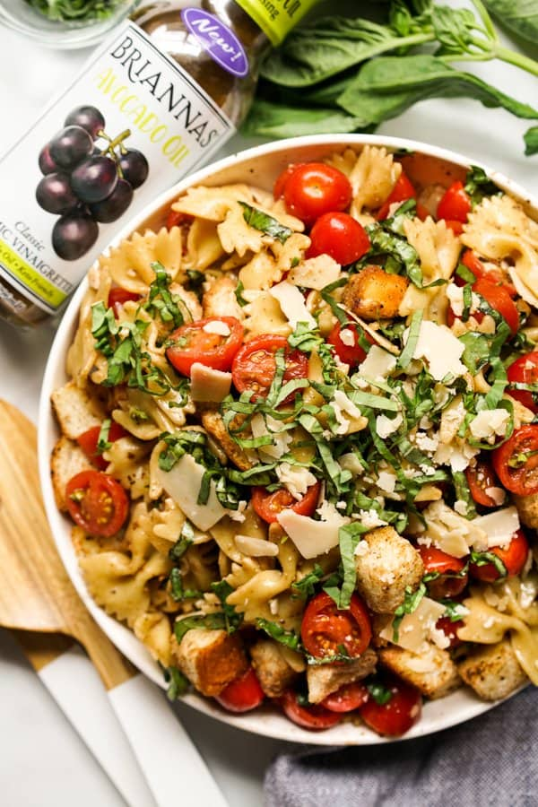 A bowl of pasta salad with tomatoes, basil and parmesan, with salad dressing on the side