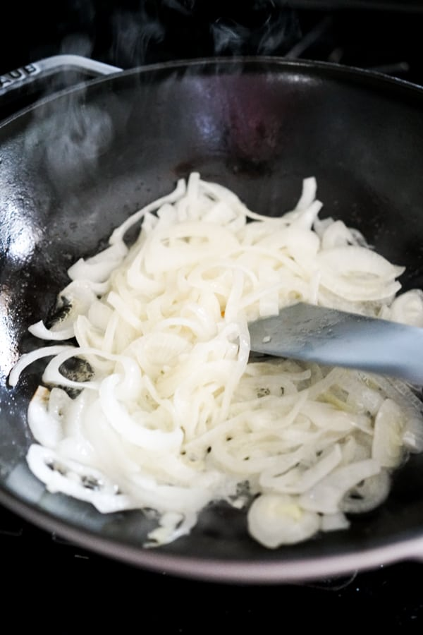 Raw white onions in a skillet