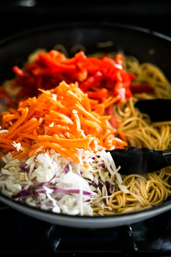 Adding carrots, red bell peppers, and cabbage