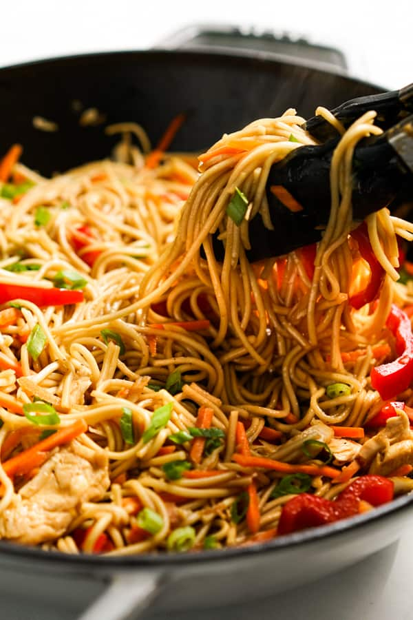 Picking up Chicken lo Mein from skillet with a pair of tongs