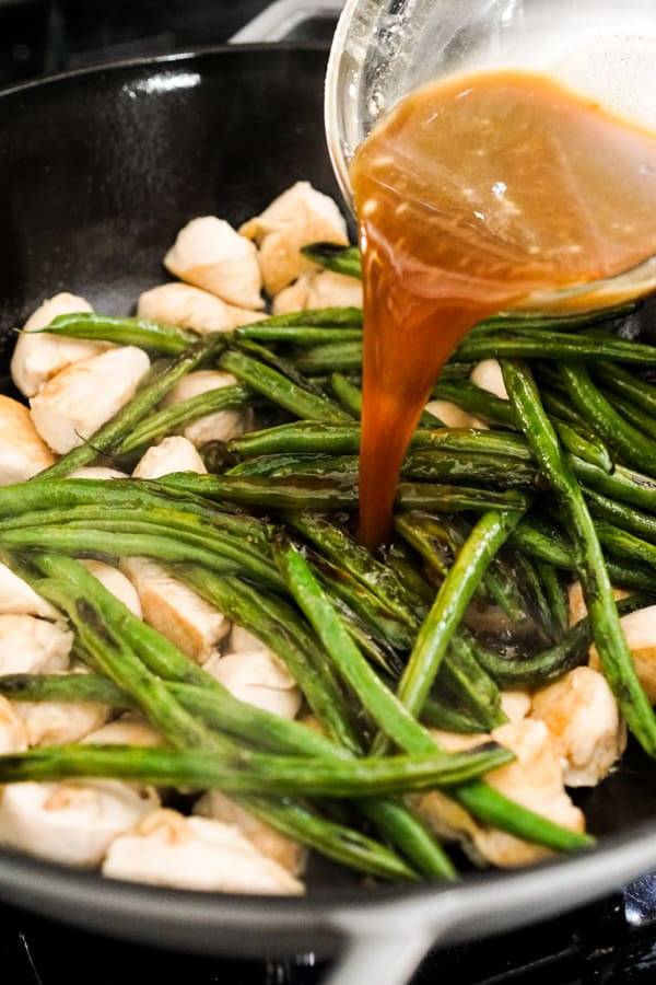 Adding Teriyaki Sauce to chicken and green beans in a skllet
