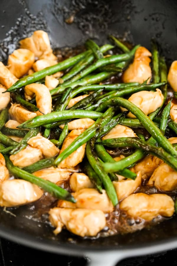 Stir frying chicken and green beans in skillet
