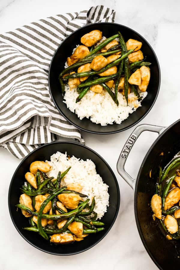 Top down view of two bowls of chicken and green beans, and a pan filled with it