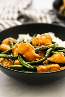 A bowl of rice topped with chicken and green beans in teriyaki sauce