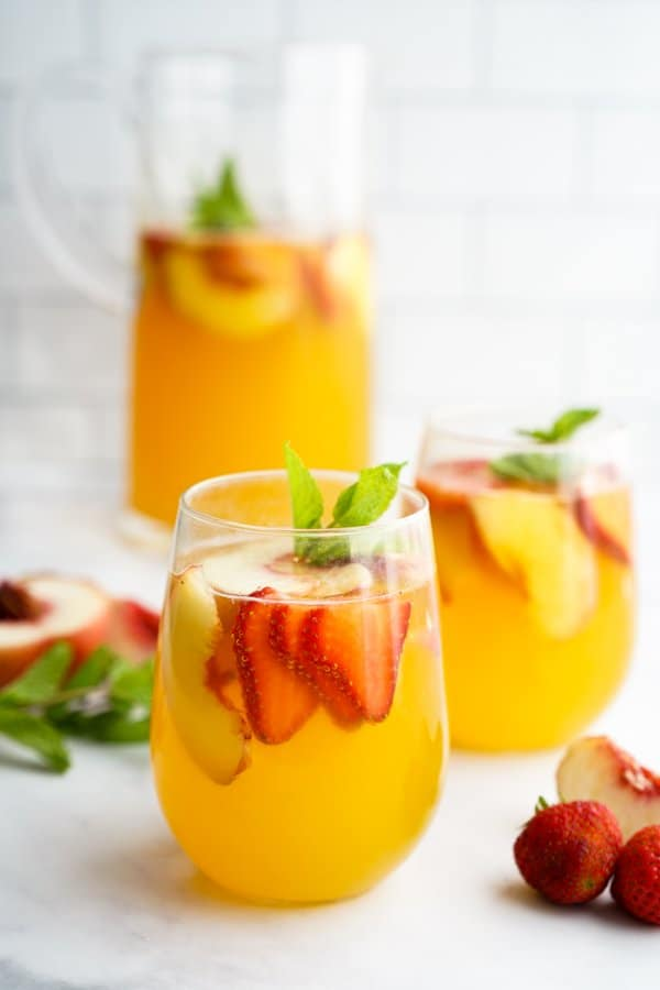 White Peach Sangria in glasses and a pitcher