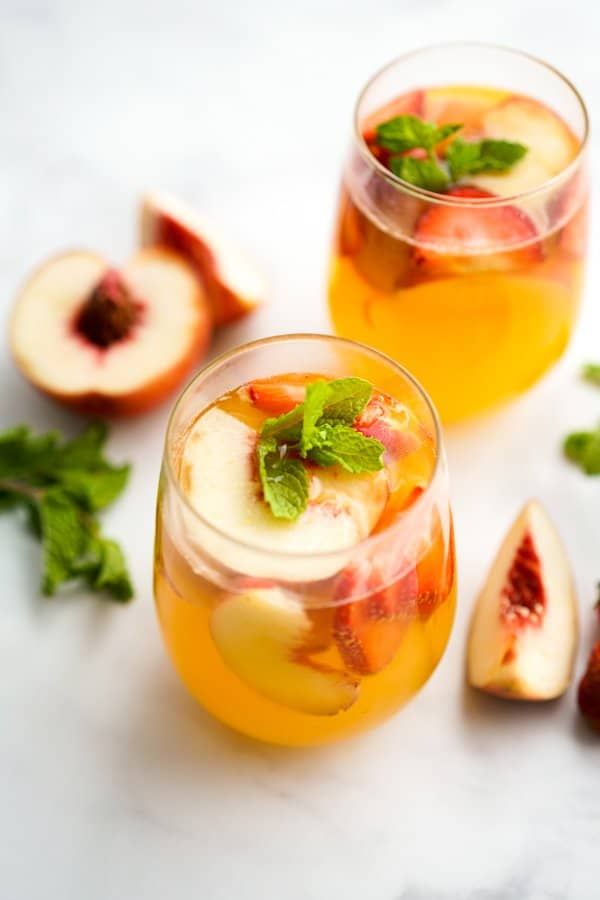 Two glasses of peach sangaria with slices of peaches around it