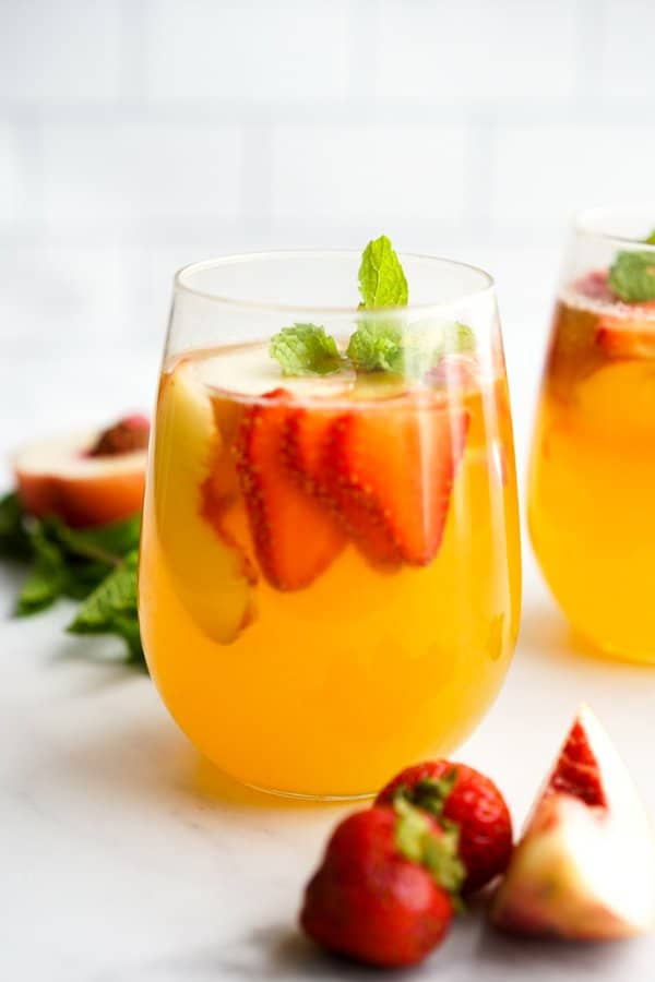 A glass of white wine sangria with fruits and mint on it