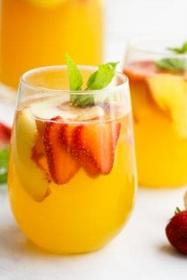 White Sangria with slices of peaches and strawberries
