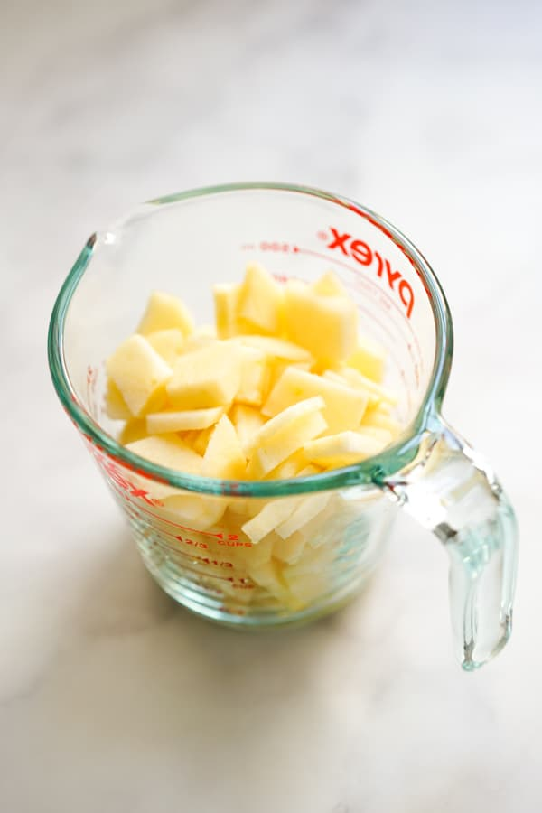 Sliced apples in a measuring cup
