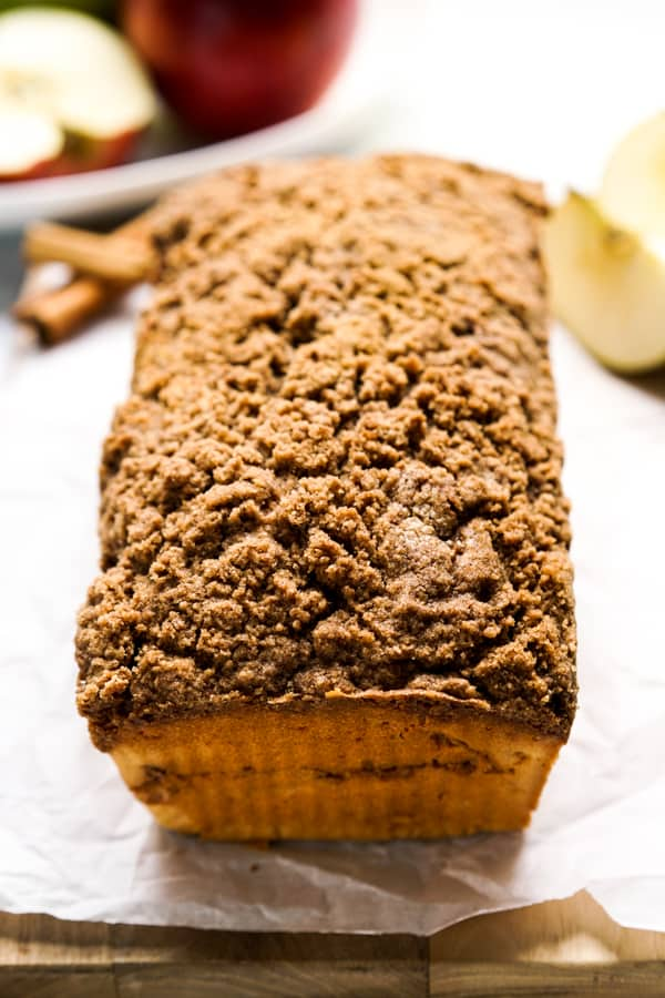A loaf of Cinnamon Apple Bread with apples in the background