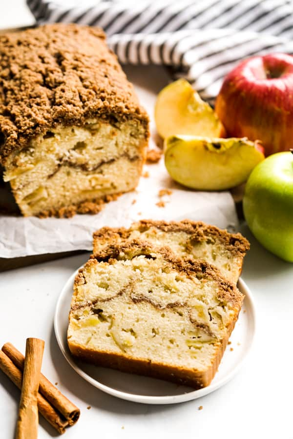 Two slices of Apple Cinnamon Bread on a plate and a loaf in the background, along with apples