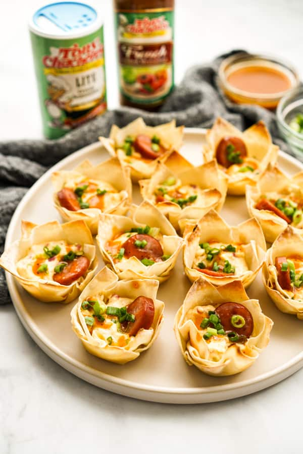 A plate of wonton cups with seasoning and sauces in the background