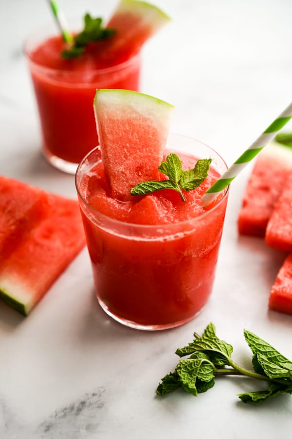 Two glasses of watermelon slush with a straw and a slice of watermelon in it