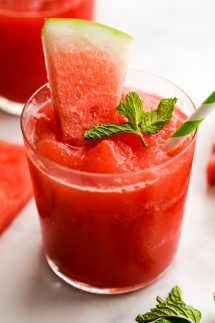 A glass of watermelon slushie with watermelons slices and mint leaves on it and around it