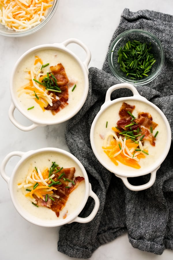 Top down view of three bowls of loaded baked potato soup