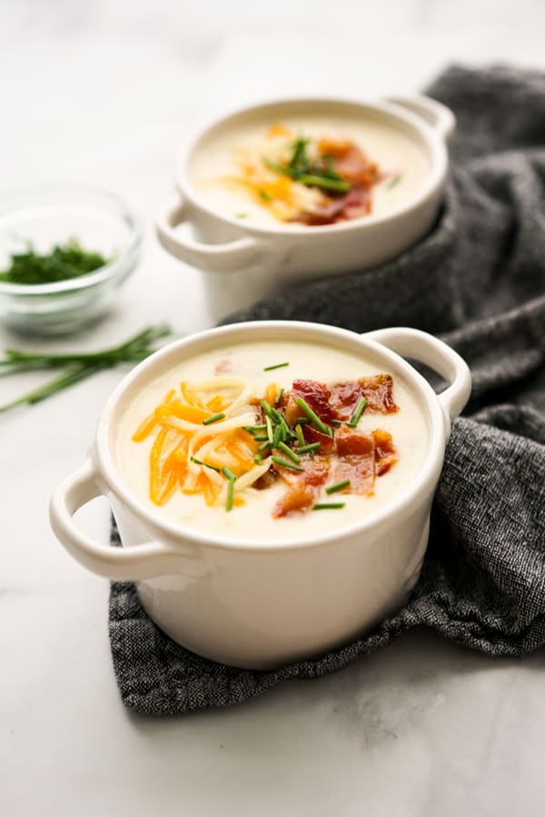 Two bowls of Creamy Potato Bacon Soup with chives in the background