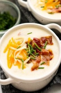 A bowl of potato soup topped with bacon, cheese and chives