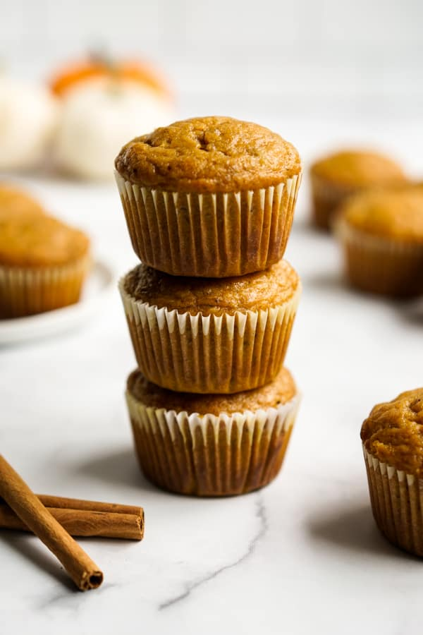 A stack of three muffins with pumpkin in the background