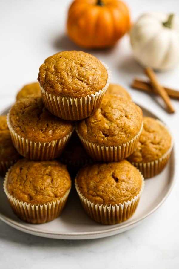 Muffins on a plate with pumpkins and cinnamon sticks in the background