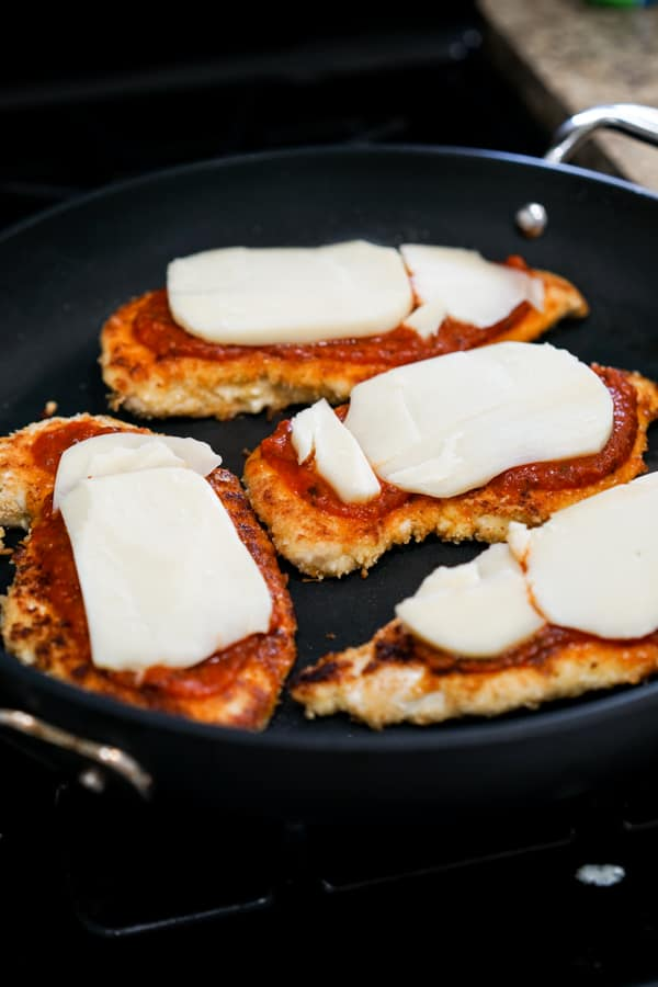 Top Chicken cutlets with red sauce and then mozzarella