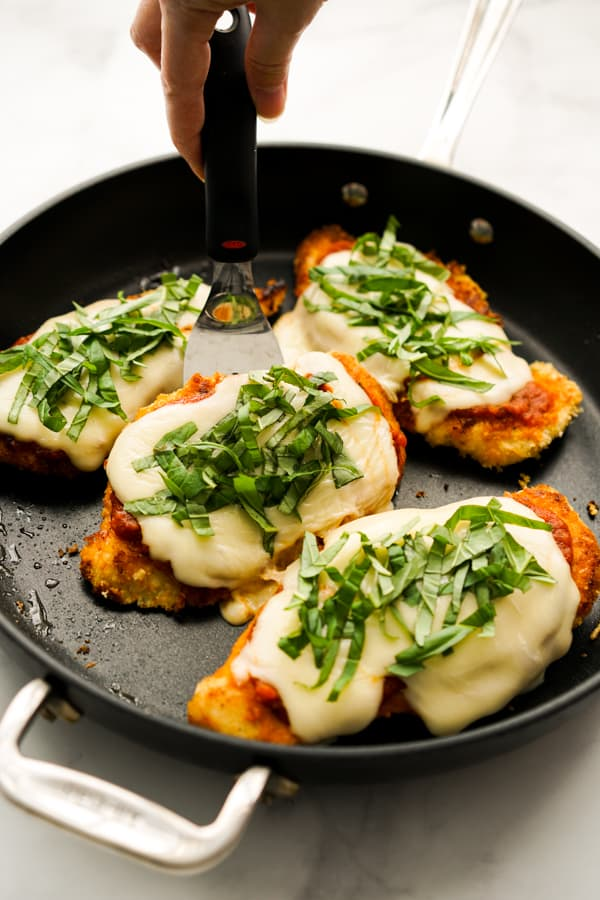 Lifting up a piece of Skillet Chicken Parmesan