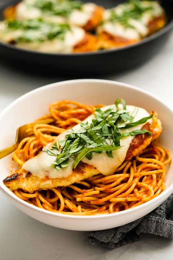 A bowl of spaghetti topped with chicken parm