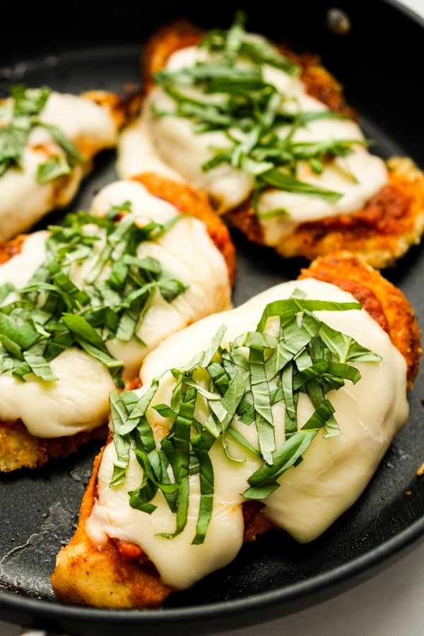 Closeup of chicken parmesan topped with marinara sauce, melted cheese and fresh basil