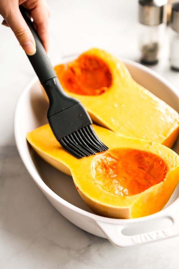 brushing olive oil on the surface of butternut squash