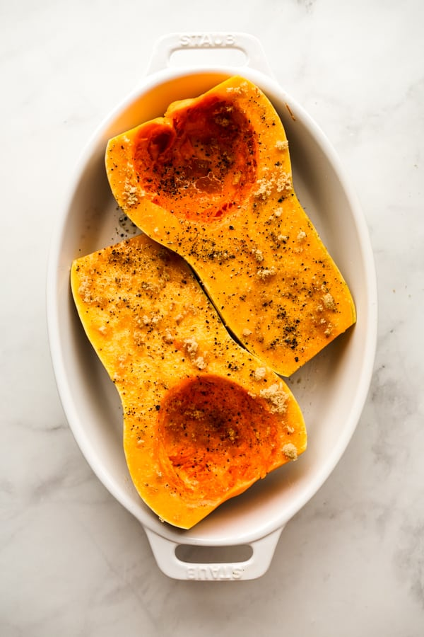 Halved whole butternut squash topped with salt, pepper, brown sugar and olive oil