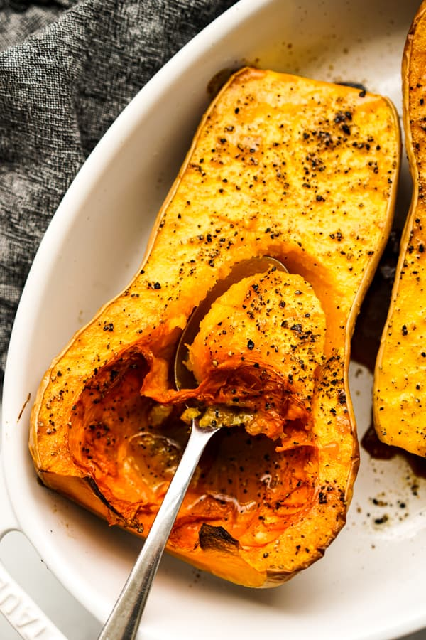 Scooping out a spoonful of Whole Roasted Butternut Squash