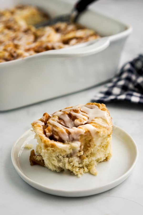 A plate of one cinnamon roll with apple pie filling