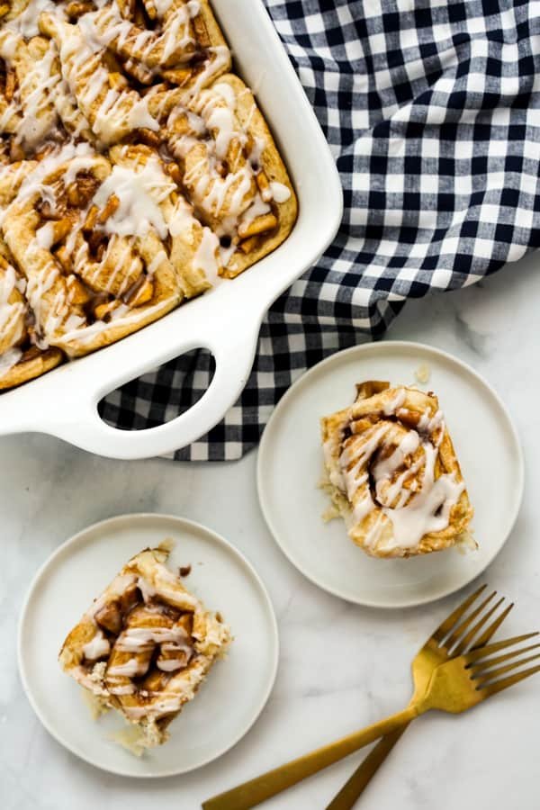 A casserole dish of cinnamon rolls and two plates of cinnamon rolls