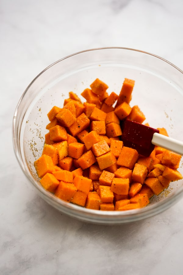 Seasoned, uncooked cubed butternut squash in a bowl