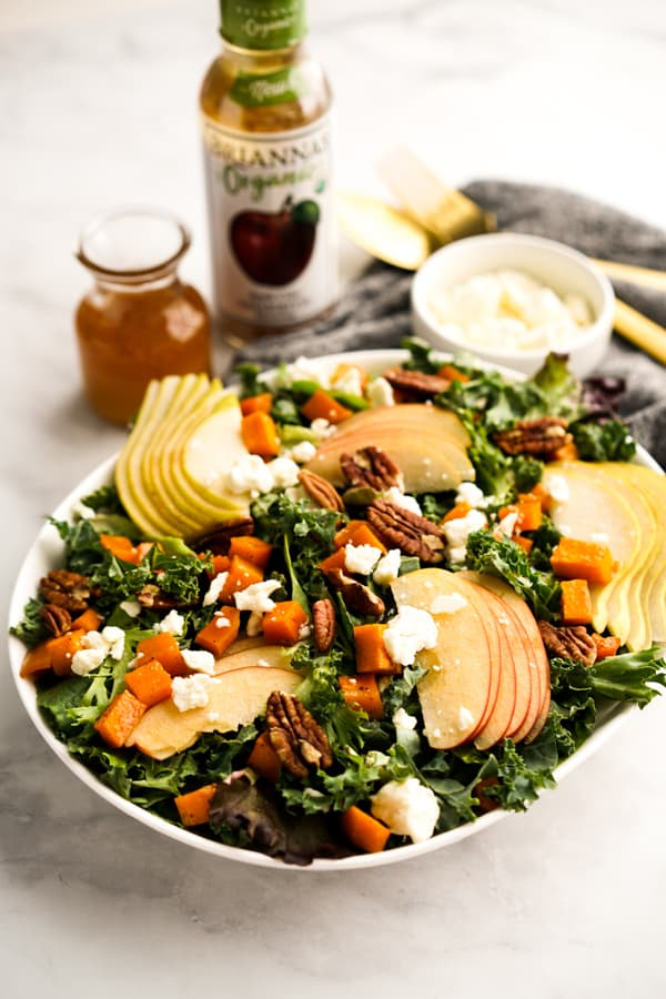 A plate of Fall themed salad with vinaigrette behind it