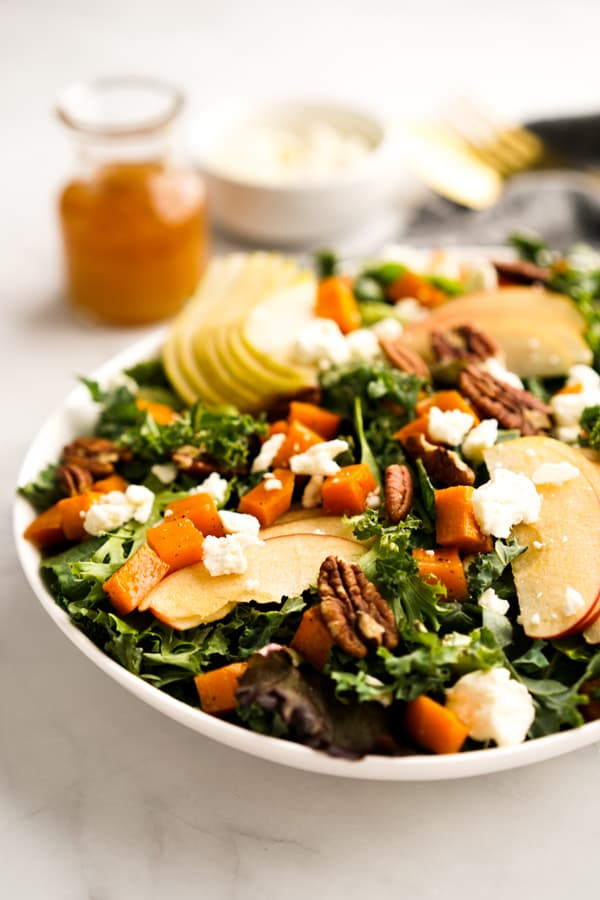 A plate of Fall Harvest Salad with dressing in the background