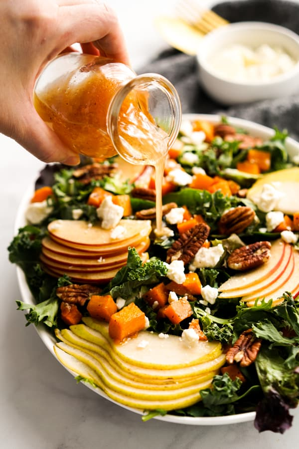 Pouring apple cider vinaigrette onto a salad topped with Fall ingredients