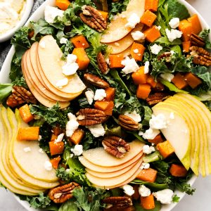 A bowl of kale and green topped with sliced apples, pears, butternut squash, and feta